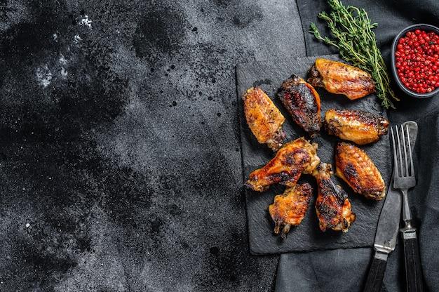 Asas de frango frito com molho. fundo preto. vista do topo. copie o espaço