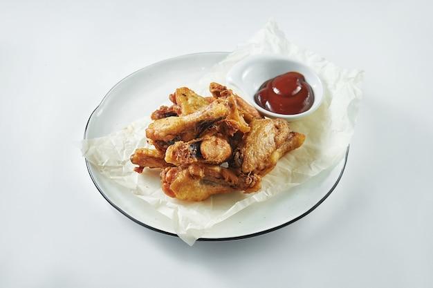 Asas de frango frito com molho vermelho em um prato branco. petisco de cerveja