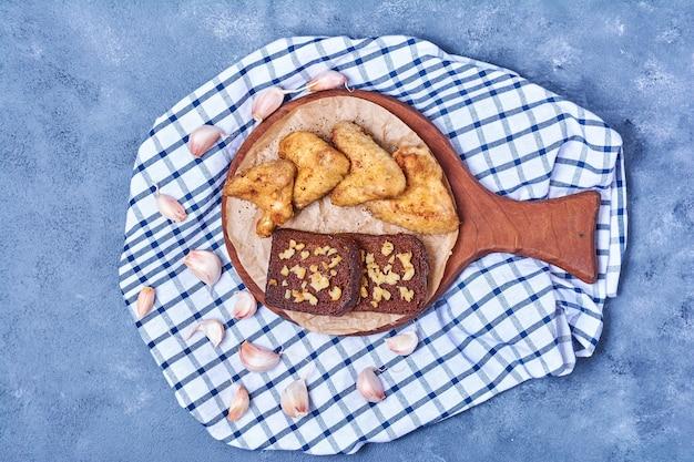 Asas de frango frito com pão em uma placa de madeira em azul