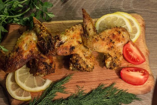 Asas de frango frito com tomate e limão em uma placa de madeira com salsa e endro
