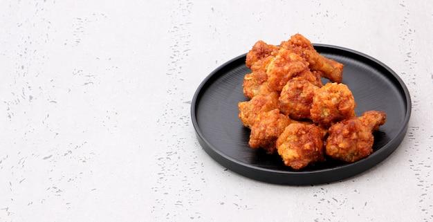 Asas de frango frito coreanas isoladas em um fundo cinza no estúdio.