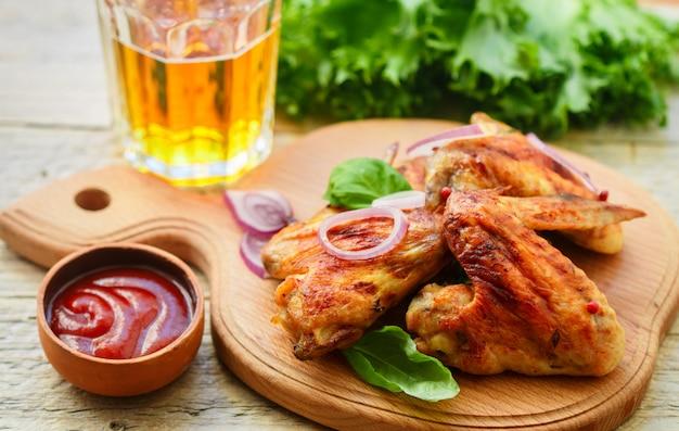 Asas de frango frito delicioso com especiarias, cebola roxa e ketchup