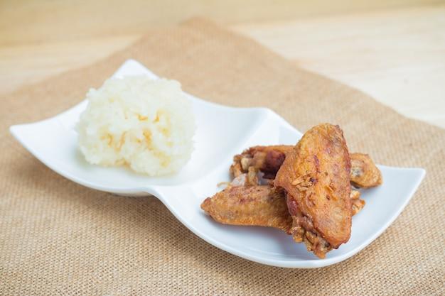 Asas de frango frito e alho crocante com arroz pegajoso (foco seletivo)