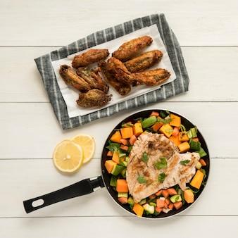 Asas de frango frito e filé com legumes