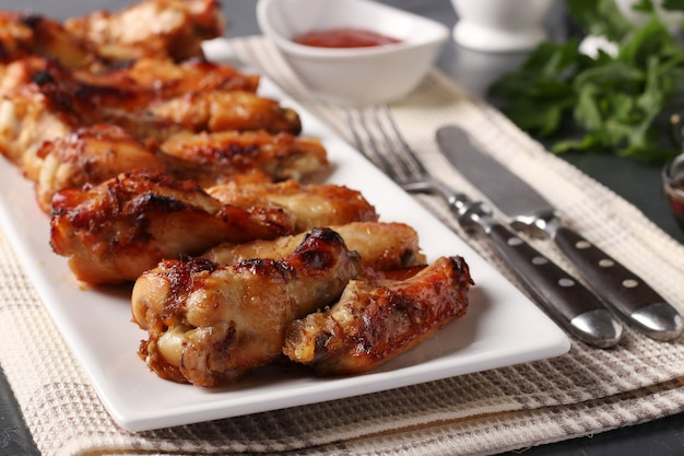 Asas de frango frito em prato branco servido com molho de tomate, close-up, formato horizontal