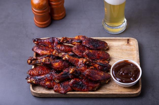 Asas de frango frito em uma placa de madeira com molho barbecue e um copo de cerveja. fundo preto, close-up.