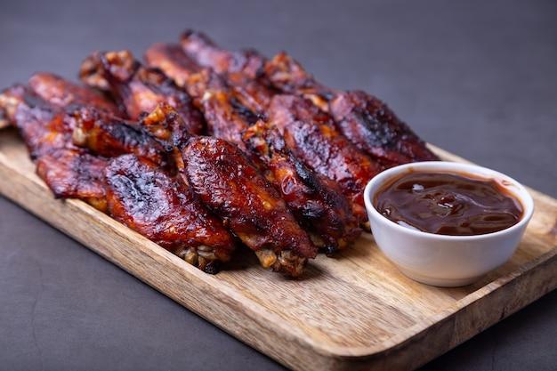 Asas de frango frito em uma placa de madeira com molho de churrasco. fundo preto, close-up.