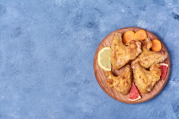 Asas de frango frito em uma placa de madeira em azul