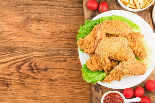 Asas de frango frito na mesa de madeira.