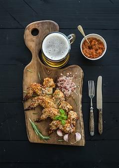 Asas de frango frito na tábua rústica, molho de tomate picante, ervas e caneca de cerveja light