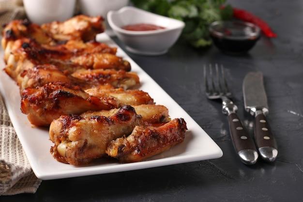 Asas de frango grelhadas em um prato branco e molho de tomate em superfície escura