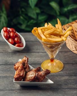 Asas de frango grelhado com batatas fritas e tomate cereja