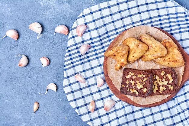 Asas de frango grelhado com especiarias e fatias de pão em uma placa de madeira em azul