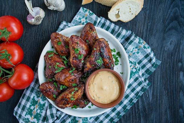 Asas de frango grelhado com molho e ervas. asas de frango assadas na panela.