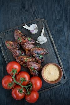 Asas de frango grelhado com molho e ervas. asas de frango assado na panela.