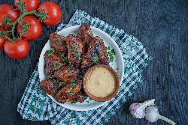 Asas de frango grelhado com molho e ervas.