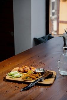 Asas de frango grelhado de churrasco fechem com batatas fritas, molho na placa de madeira. conceito de comida de carne. coxas de frango fritas com batatas fritas