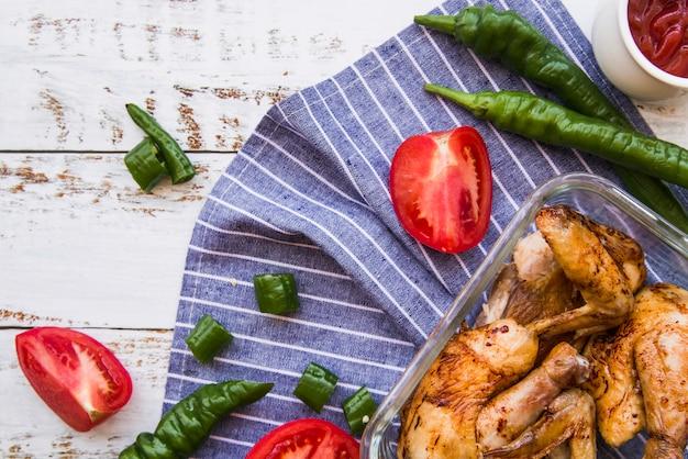 Asas de frango grelhado e fatias de tomate; pimentões verdes na mesa de madeira