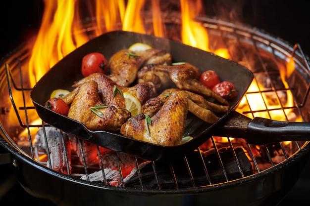 Asas de frango grelhado na grelha em chamas com legumes grelhados em molho barbecue com sementes de pimenta alecrim, sal. vista superior com espaço de cópia.
