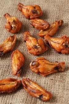 Asas de frango grelhado numa toalha de mesa de linho