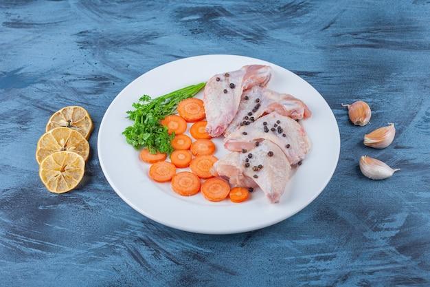 Asas de frango marinadas e vários vegetais em um prato na superfície azul