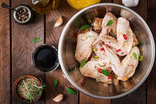 Asas de frango marinado cru, preparadas em estilo asiático com mel, alho, molho de soja e ervas.