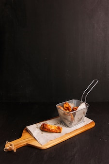 Asas de frango na tábua de madeira