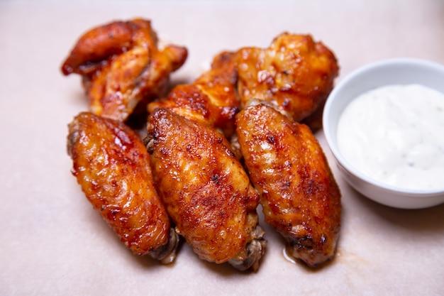 Asas de frango para churrasco com molho no papel. close-up, foco seletivo.