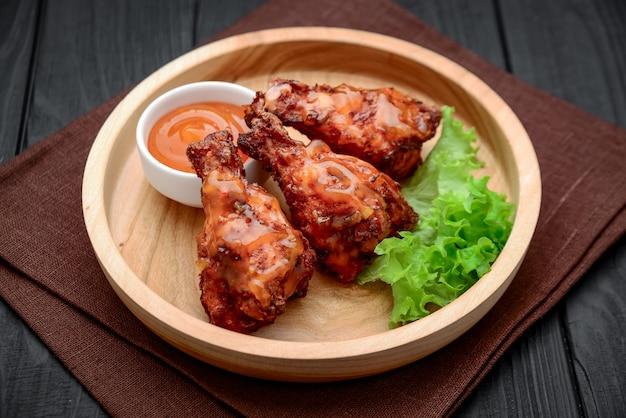 Asas de frango para churrasco com molho picante de pimenta em um prato de madeira