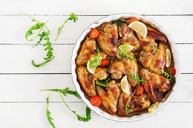 Asas de galinha cozidas na placa na tabela de madeira. vista do topo.