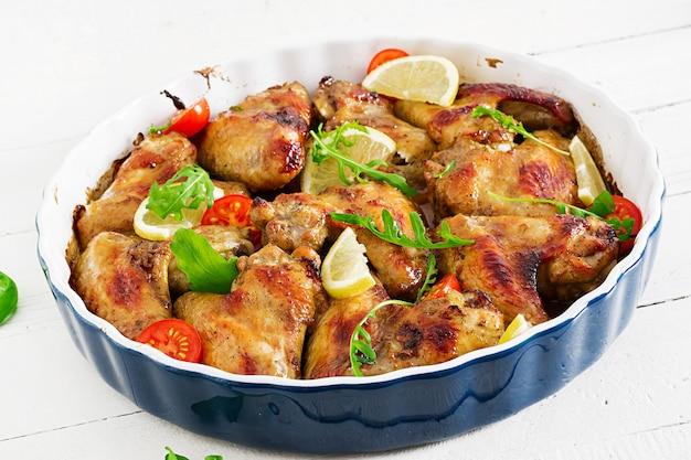 Asas de galinha cozidas na placa na tabela de madeira.