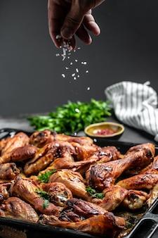 Asas e pernas de frango quentes com aipo, cook mão polvilhando salada com carne em um movimento de congelamento. fundo de receita de comida. fechar-se.