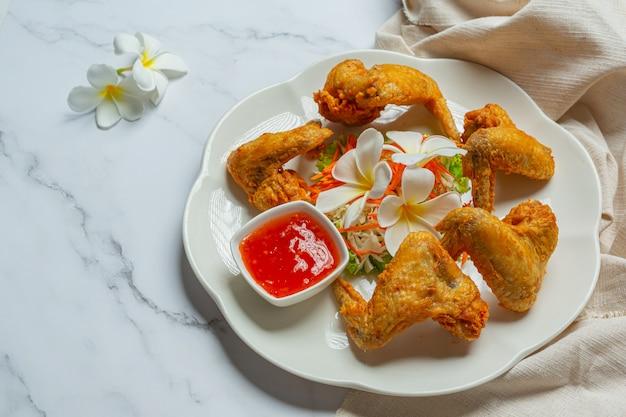 Asas fritas com molho de peixe, bem decorado e servido.