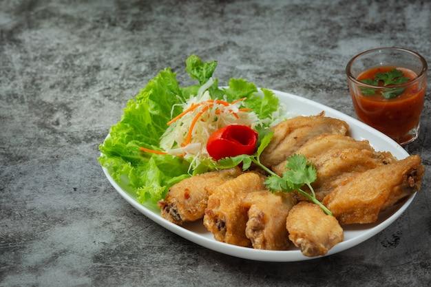 Asas fritas com molho de peixe, ervas lindamente decoradas e servidas.