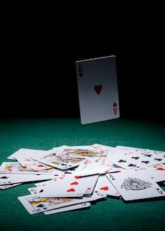 Ases cartão no ar sobre as cartas de jogar na mesa de poker verde