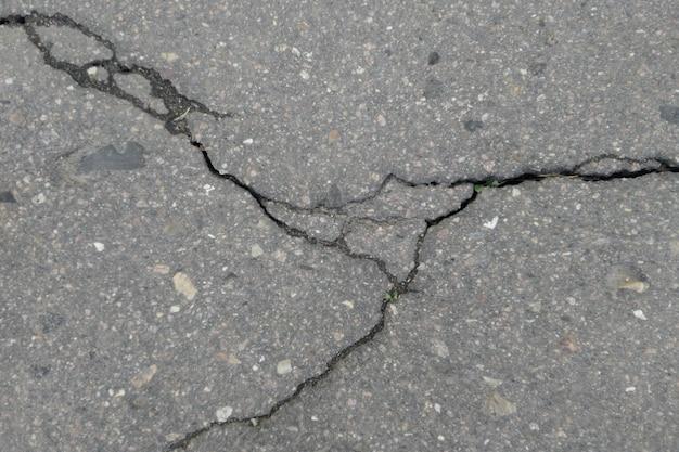 Asfalto desgastado e rachado velho com fundo das rachaduras. estrada de asfalto danificada