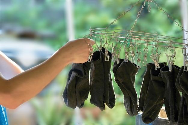 Ásia adolescente está pendurando a meia preta no clipe de roupa seca após a lavagem.