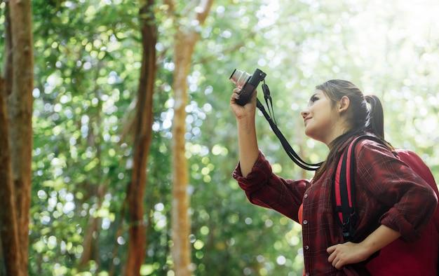 Ásia caminhadas tirando foto na natureza.