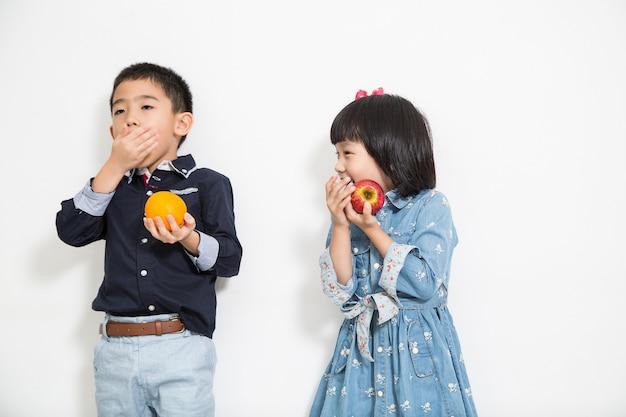 Ásia garoto, menino e menina comendo fundo branco de frutas.