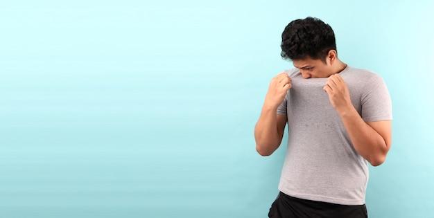 Ásia homem suando excessivamente mau cheiro isolado na parede azul.