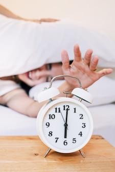 Asia woman sleepy não quer acordar às 6:00 da manhã com um despertador.