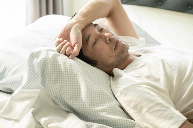 Asiam sênior homem dormindo na cama