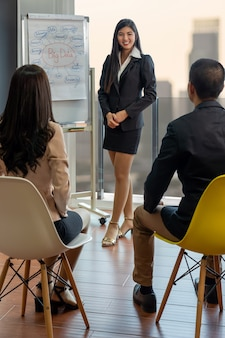 Asian busiensswoman apresentando os dados grandes sobre o gráfico para colegas de trabalho em equipe com moder