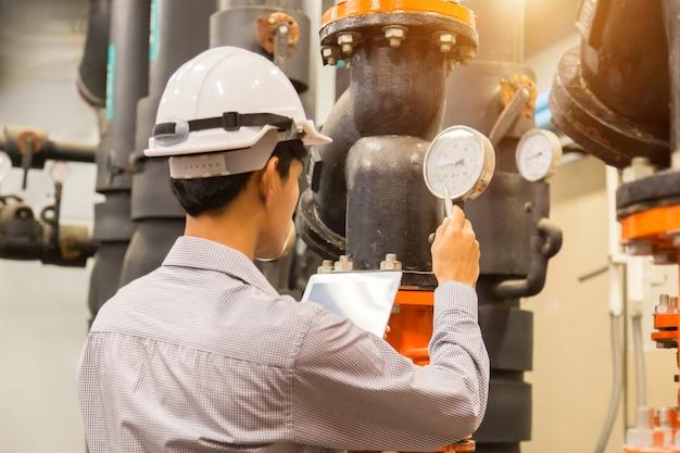 Asian engineer maintenance checking medidor de pressão de condensador de água