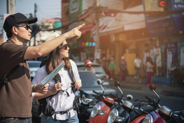 Asiancouple turista segurando o mapa da cidade atravessando a estrada