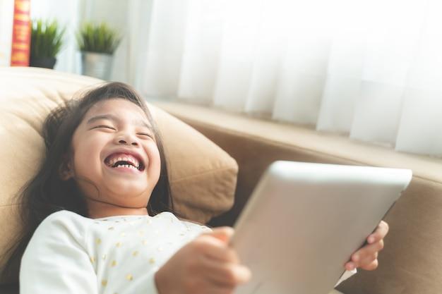 Asiática bonita criança brincar com um tablet e sorrindo enquanto está sentado no sofá em casa