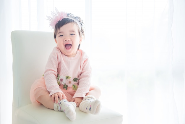 Asiática bonito menina sentada e sorri na cadeira