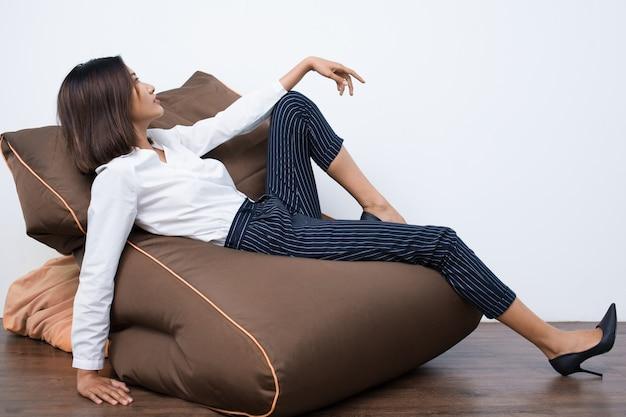 Asiática consideravelmente nova mulher que descansa na beanbag chair