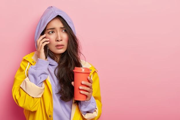 Asiática descontente com bochechas rosadas, tem expressão facial nervosa, liga para namorado pelo smartphone, tenta se aquecer com café para viagem