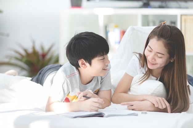 Asiática irmã e irmão relaxante e jogando na cama ther